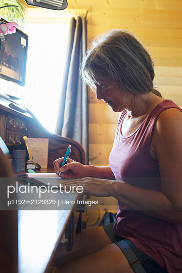 Mature woman writing in notebook with pen in motorhome - p1192m2129329 by Hero Images