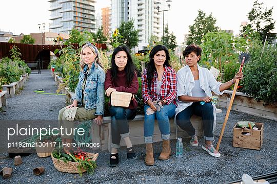 Portrait confident mature women friends in urban community garden - p1192m2130117 by Hero Images