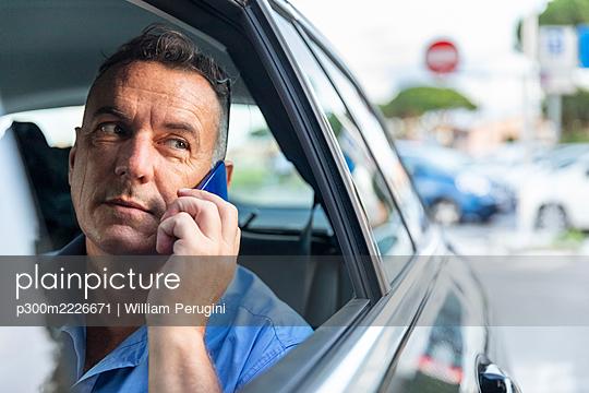 Mature male entrepreneur talking through mobile phone while sitting in car - p300m2226671 by William Perugini