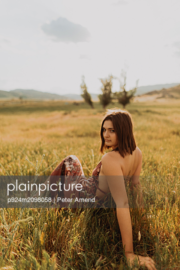 Beautiful young woman sitting in field of long grass looking over her shoulder, portrait, Exeter, California, USA - p924m2098058 by Peter Amend