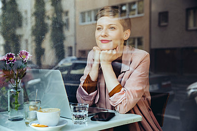 Woman with her laptop enjoying the view in a cafe - p300m1505867 by Mareen Fischinger