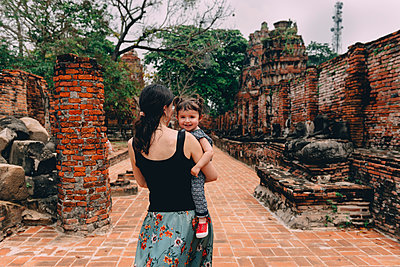 Thailand, Ayutthaya, Mother and daughter walking through the ancient ruins of a temple at Wat Mahathat - p300m2058800 von Gemma Ferrando