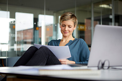 Smiling businesswoman working at desk in office - p300m2181093 by Rainer Berg