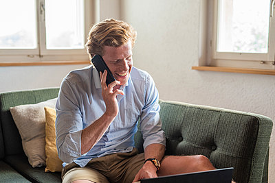 Happy freelance worker talking on smart phone at home - p300m2243824 by MaxwellArt Photography