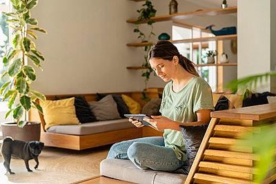 Young woman using digital tablet while sitting on sofa at home - p300m2267395 by Steve Brookland