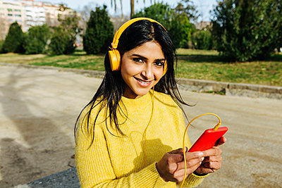 Smiling beautiful woman holding mobile phone while listening music through headphones in public park - p300m2268309 by Xavier Lorenzo