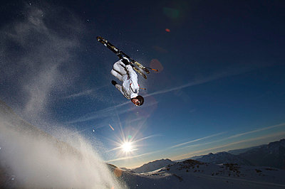 Skier back flipping off a rock. - p4295478 by Ross Woodhall
