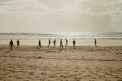 Football players on a beach - p445m1552773 by Marie Docher
