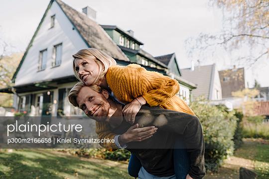 Man giving his wife a piggyback ride in garden - p300m2166658 by Kniel Synnatzschke
