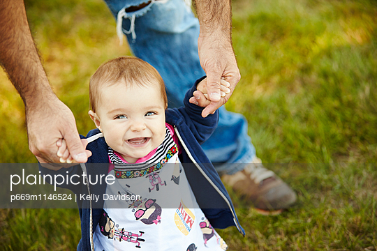 Baby Girl Taking First Steps in Garden - p669m1146524 by Kelly Davidson