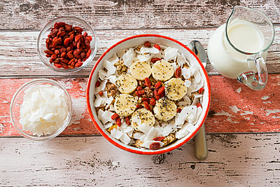 Bowl of muesli with banana slices, chia seeds, coconut chips and goji berries - p300m1101062f by Sandra Roesch