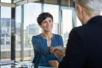 Two businesswomen shaking hands at desk in office - p300m2081110 von Rainer Berg