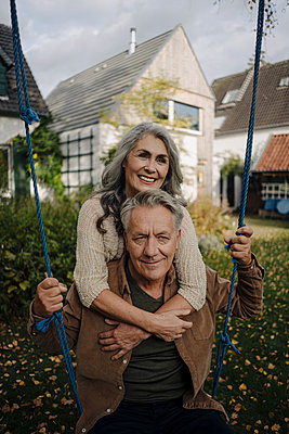 Happy woman embracing senior man on a swing in garden - p300m2154984 by Gustafsson