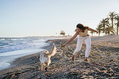 Woman playing with dog on sand by sea against sky during weekend - p300m2267794 by Manu Padilla Photo