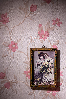 Picture frame with old photograph hanging on wallpaper with pink floral design - p300m980228 by EJW