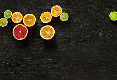 Citrus fruits on black background - p312m2091616 by Pernille Tofte