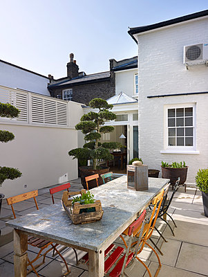 Tree in large plant pot, table and chairs in paved back yard of residential house, Burlington Road, London, England, UK - p855m909029 by Alistair Nicholls