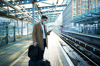 UK, London, Man waiting at train station platform - p924m2271232 by Peter Muller