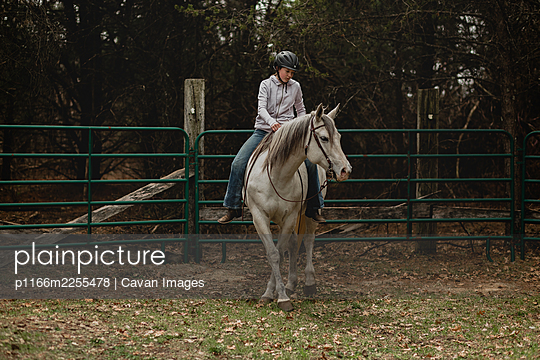 Teen girl riding grey mare bareback in round pen - p1166m2255478 by Cavan Images