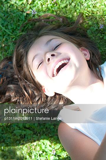 Mädchen liegt lachend auf Wiese - p1311m2013911 von Stefanie Lange