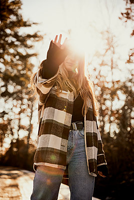 Young woman gesturing while standing at park during sunny day - p300m2250076 by Aitor Carrera Porté
