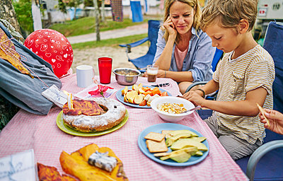 Family at picnic table celebrating boys birthday, Florianopolis, Santa Catarina, Brazil, South America - p429m1519604 by Stephen Lux