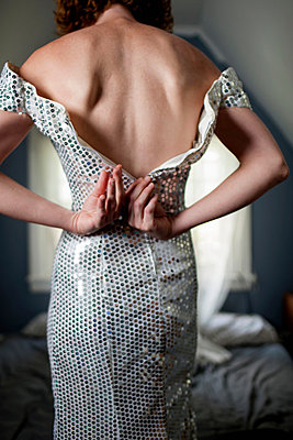Close up of woman in bedroom unzipping evening gown - p429m839074 by Zave Smith