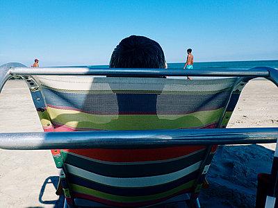 Mann im Liegestuhl am Strand - p988m2015072 von Rachel Rebibo