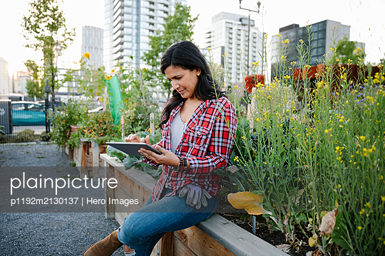 Woman using digital tablet in urban community garden - p1192m2130137 by Hero Images