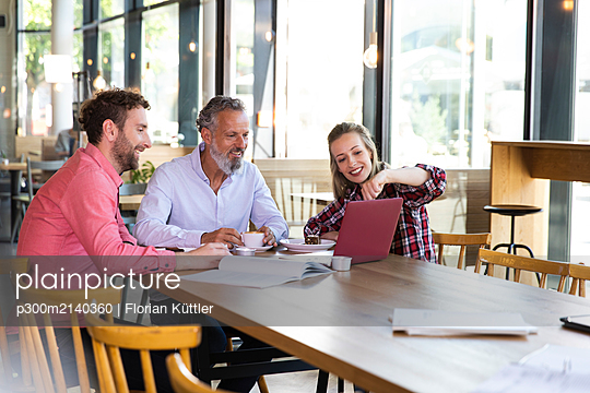 Casual business people having a meeting in a cafe - p300m2140360 by Florian Küttler