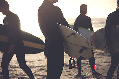 Four men wearing wetsuits standing on a sandy beach, carrying surfboards. - p1100m2214274 by Mint Images