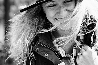 woman laughing with her hair blowing in the wind - p1166m2212901 by Cavan Images