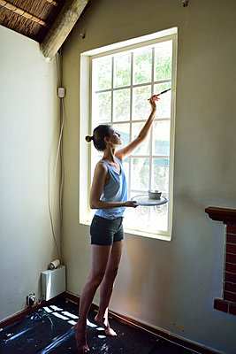 Young woman renovating her home painting the window frame - p300m2079215 by Eyecatcher.pro
