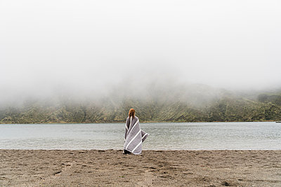 Woman wrapped in blanket standing at lakeshore in Sao Miguel Island, Azores, Portugal - p300m2197217 by VITTA GALLERY