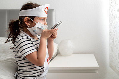 Girl in a doctor's costume wearing a mask and calling - p300m2198087 by Ezequiel Giménez