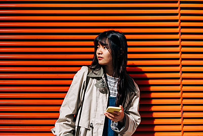 Woman with bangs holding smart phone in front of orange wall - p300m2298822 von Angel Santana Garcia