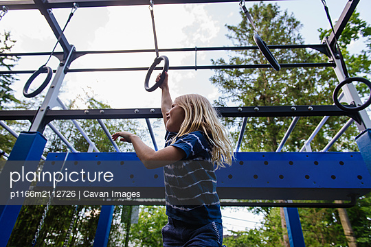 Girl swinging on rings on playground - p1166m2112726 by Cavan Images