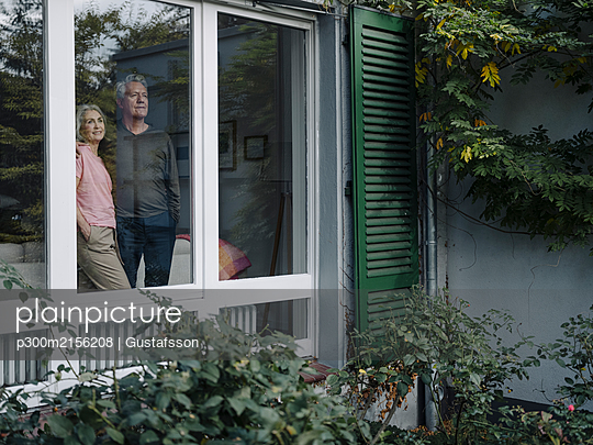 Senior couple behind windowpane of their home looking out - p300m2156208 by Gustafsson