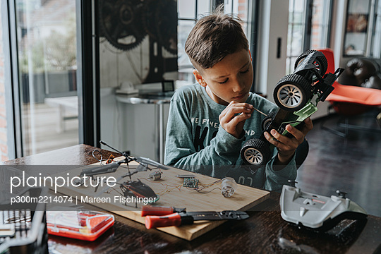 Boy assembling on remote-controlled toy car with screwdriver - p300m2214074 by Mareen Fischinger