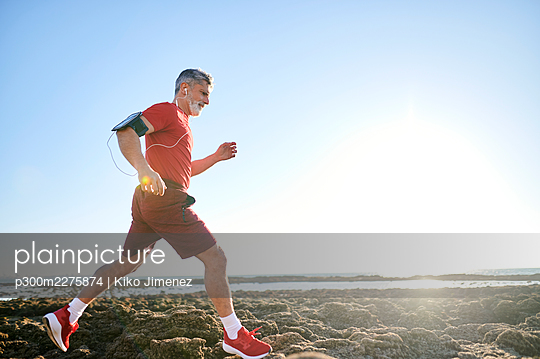 Male runner jogging on rocks at beach - p300m2275874 by Kiko Jimenez