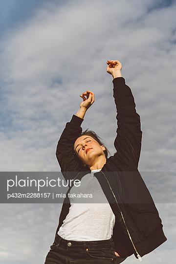 Frau genießt die Sonne auf Dach - p432m2288157 von mia takahara