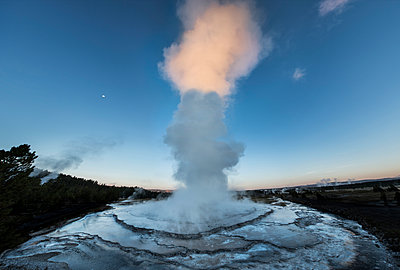 Steam emitting from geyser against blue sky at dusk - p1166m1193885 by Cavan Images