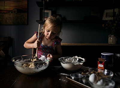 Girl mixing batter in bowl on table at home - p1166m1553337 by Cavan Images