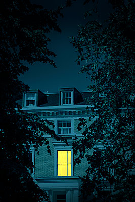 Illuminated window of a house at night - p1248m2187199 by miguel sobreira