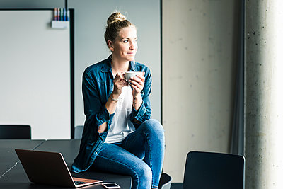 Smiling businesswoman sitting on table in office having a coffee break - p300m2132545 by Uwe Umstätter