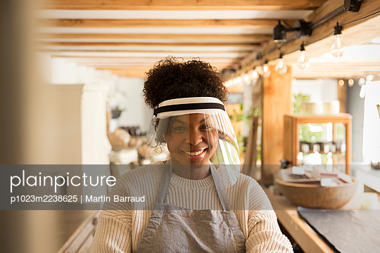 Portrait happy female shop owner wearing face shield - p1023m2238625 by Martin Barraud