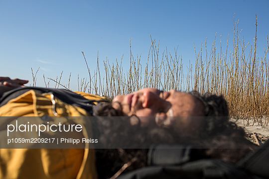 Woman sleeping in the dunes - p1059m2209217 by Philipp Reiss