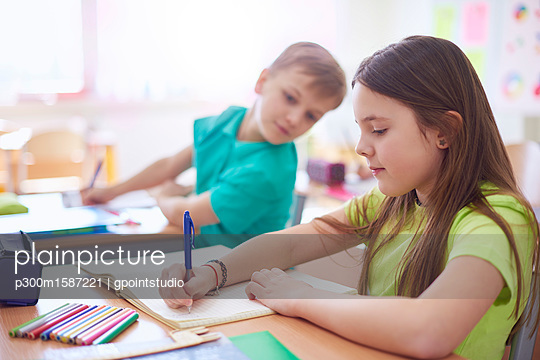 Schoolboy looking at schoolgirl writing in exercise book in class - p300m1587221 von gpointstudio