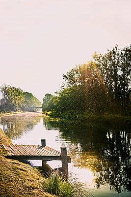 River bank on the canal with wooden jetty - p1312m2258018 by Axel Killian