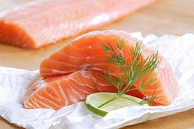 Raw salmon on foil with slice of lemon - p30020465f by Dieter Heinemann